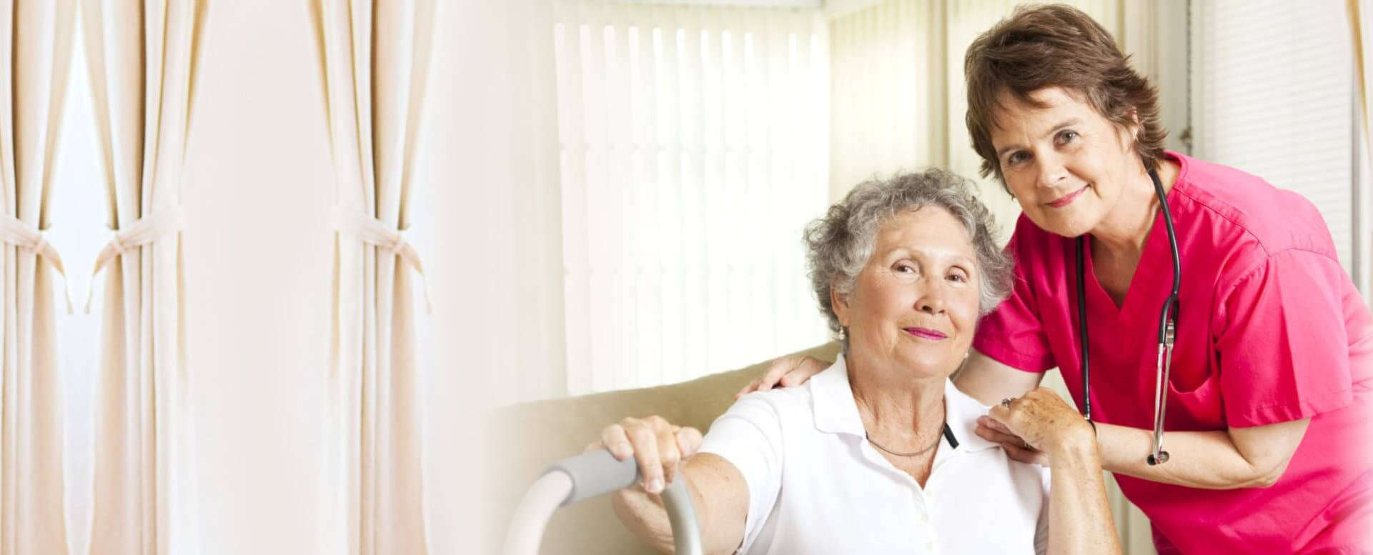 senior woman sitting on the couch with caregiver