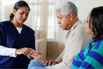 caregiver giving senior man a medication